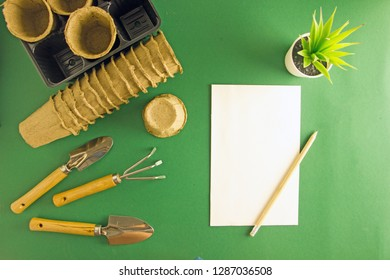 Garden tools, cups for seedlings, sheet for notes, pencil, background about gardening, background about agriculture, home floriculture