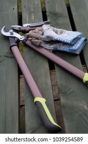 Garden tools and garden gloves on a wooden garden table