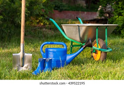 Garden tools on a green lawn. watering can and rubber boots.