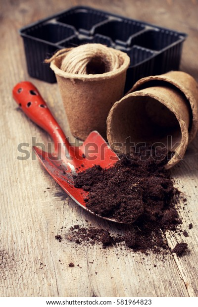 garden tools, peat pots, ground  for planting  on the old wooden background