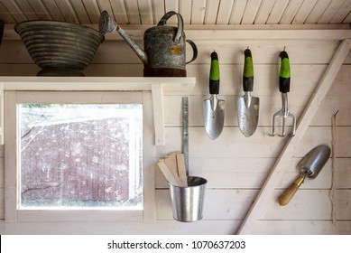 Garden tools in a small storage shed. Shovels, rake, water pitcher and all you need for gardening.