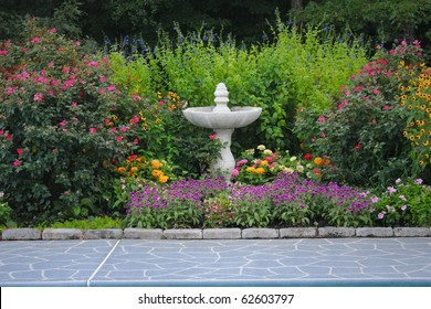 A garden walk bordered with a colorful variety of flowers and a bird bath