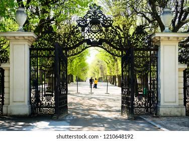 Garden Walkway at Schonbrunn Palace in Vienna, Austria. Black metallic opened gates and white columns people walking along park