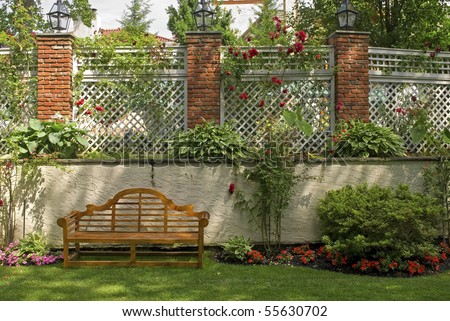 A Garden Wall With A Trellis And Red Rose Bushes.