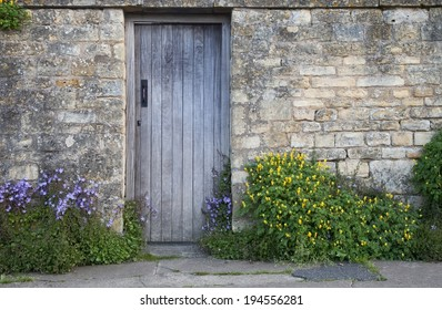 Garden wall with wooden door and flowers, Cotswolds, Chipping Campden, Gloucestershire, England.