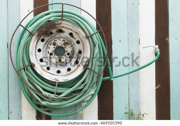 Garden water hose reel hung on a colorful vintage wood wall