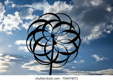 Garden Whirligig Silhouetted Against a Blue and Cloudy Sky