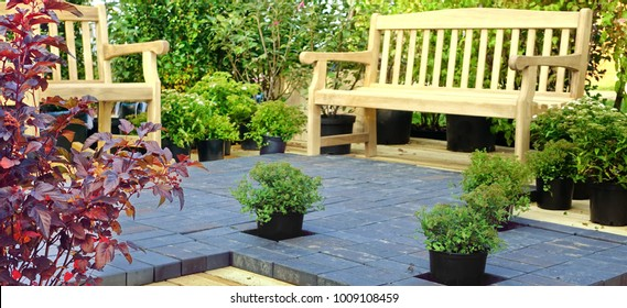 Garden Wooden Furniture On The Modern Design Patio Decking. Wooden Patio Decking With Cobblestone Bricks, Hardwood Bench And Armchair. Backyard Patio Floor Design With Natural Wooden Boards And Stone.