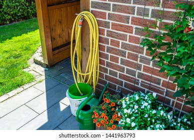 A garden yellow hose connected to a tap protruding from a farm building against a background of brick facade, visible plastic watering can, bucket and flowers.