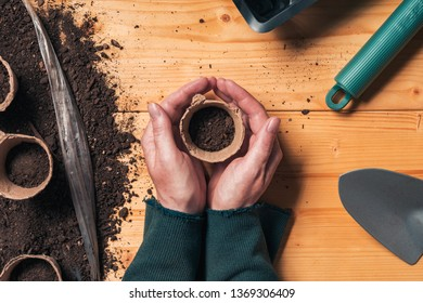 Gardener with biodegradable soil pot container in hands directly above the table with organic farming and gardening equipment for homegrown food production, top view