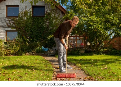 gardener cleaning a garden path and removing leaves with a red broom