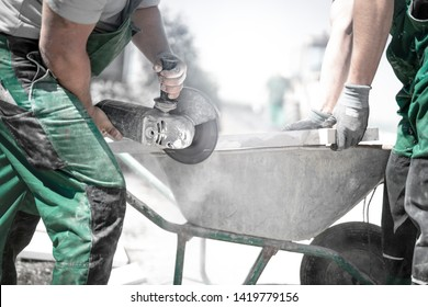 Gardener cuts stone slab with the angle grinder in a garden and his apprentice helps him