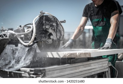 Gardener cuts stone slab with big stone saw with water cooling
