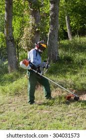 Gardener cutting grass with string trimmer