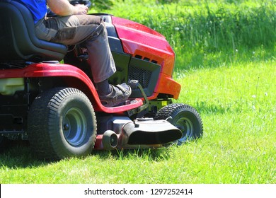 Gardener driving a riding lawn mower in a garden .
