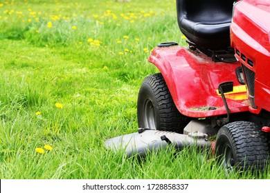 Gardener driving a riding lawn mower in a garden . Cutting grass .