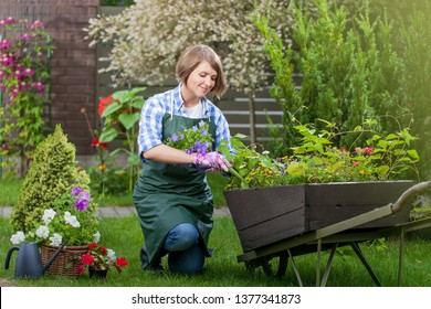 gardener or florist at work. smiling young woman planting flowers in the yard. garden worker trimming plants. topiary art. gardening service and business concept
