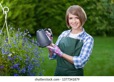 gardener or florist at work. smiling young woman planting flowers in the yard. garden worker trimming plants. gardening service and business concept
