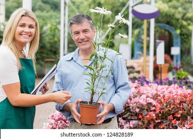 Gardener giving advice to customer while holding a flower and smiling