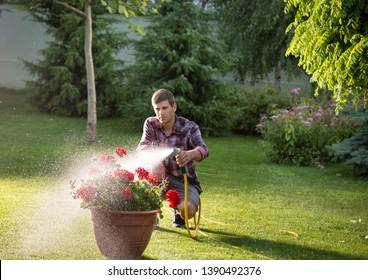 Gardener holding hand hose sprayer and watering flowers in garden