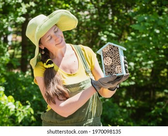 Gardener is holding a house for bees or other pollinators.