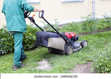 A gardener mowing the grass with a lawn mower