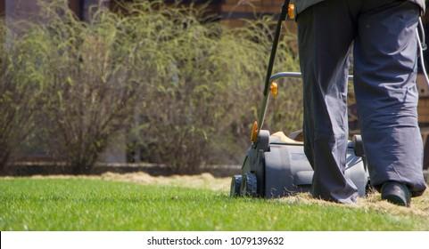 Gardener Operating Soil Aeration Machine on Grass Lawn