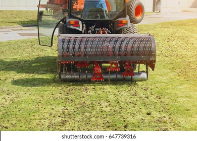 Gardener Operating Soil Aeration Machine on Grass Lawn