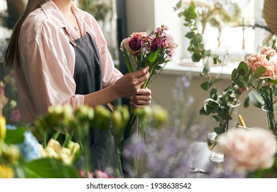 Gardener s in the flower shop make bouquet for a holiday. Lifestyle flower shop. Beautiful flower composition. Detail. Close up