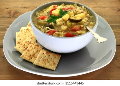 Gardener style gourmet vegetables vegetarian soup with added noodles  served with salty soda crackers side in grey porcelain bowl over plate on wooden garden table decorated with struck plain parsley