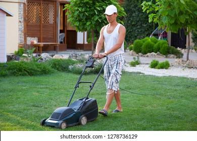 Gardener using garden equipment. Man mowing green grass with electric lawn mower