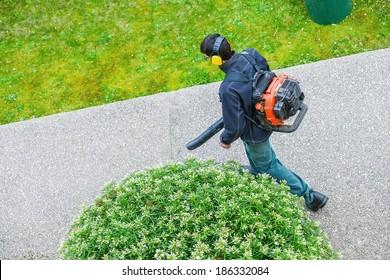 jardinier utilisant un souffleur à gaz dans un parc