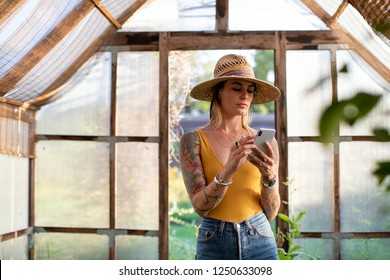 Gardener using her phone in the greenhouse