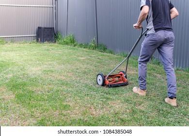 gardener using push mower to cut the grass
