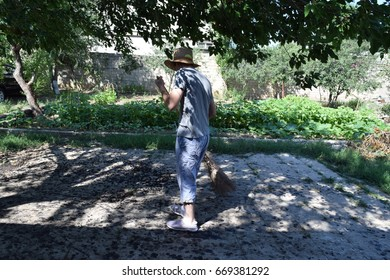 gardener at work, cleaning a garden path.with a red broom