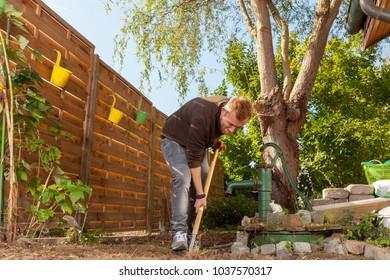 gardener at work digging over garden soil