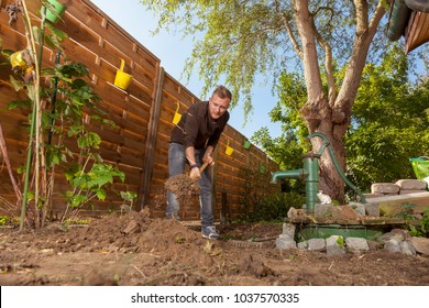 gardener at work digging over garden soil