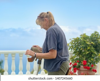 A gardener at work with the electric edge, she is wearing work clothes, lateral back view and she is cleaning her equipment.