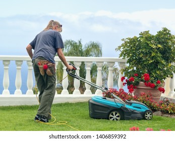 A gardener at work with the electric lawn mower, she is wearing work clothes, lateral back view.