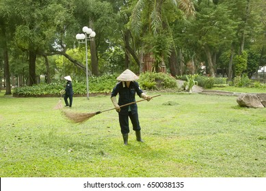 Gardeners are cleaning and sweeping a lawns, Tao Dan park, Ho Chi Minh city, Vietnam.