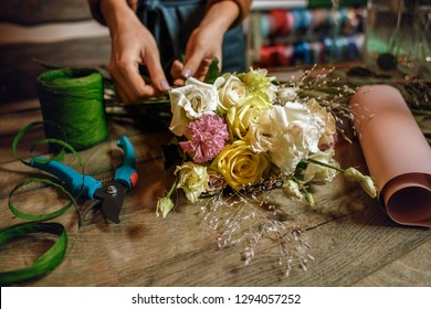 Gardener's in the flower shop make bouquet for a holiday. Family flower's business.  Lifestyle flower shop. Beautiful flower composition. Detail. Close up.