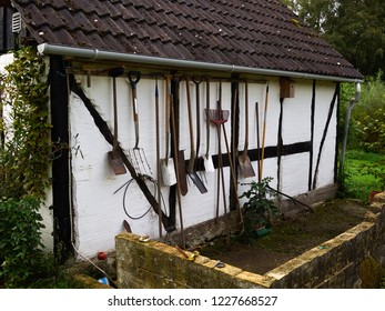 Gardening aging tools hanging on a wall of an old traditional country house