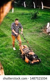 Gardening details, industrial gardener working with lawnmower and cutting grass in garden