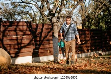 Gardening details - industrial worker using leaf blower
