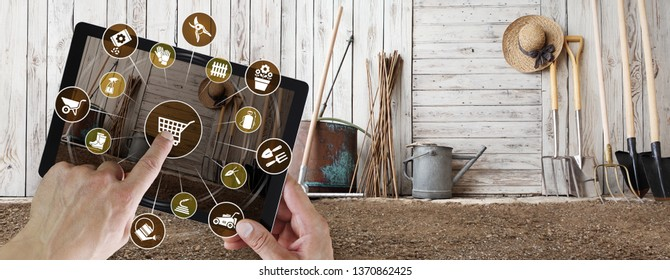 gardening equipment e-commerce concept, online shopping on digital tablet, hand pointing and touch screen with garden tools icons, tool shed in the background