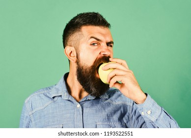 Gardening and fall crops concept. Guy presents homegrown harvest. Farmer with hungry face eats fresh apple. Man with beard bites green fruit isolated on green background