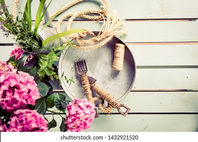 Gardening flat lay. Set of rustic, vintage gardening tools, marine rope, metal tray, watering can and pink hortensia blossoms bouquet on mint green wooden table