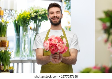 gardening, floristry and people concept - happy smiling male seller or florist in apron with bunch of peonies over flower shop background