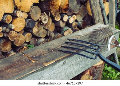 Gardening fork with copy space on the old log on the background of wood. Cleaning tool in the garden