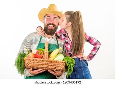 Gardening and harvesting. Family farm organic vegetables. Father farmer or gardener with daughter hold basket harvest vegetables. Man bearded rustic farmer with kid. Farmers family homegrown harvest.